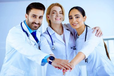 Multiracial medical team stacking hands in hospital