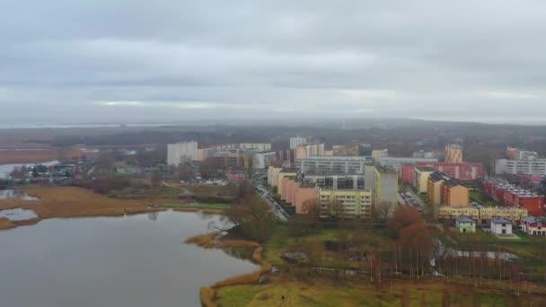 Letecké záběry z bezpilotních letounů letí směrem k obytným činžovním domům. Voda a park.