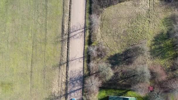 Letecký pohled shora dolů na auto jedoucí po štěrkové cestě