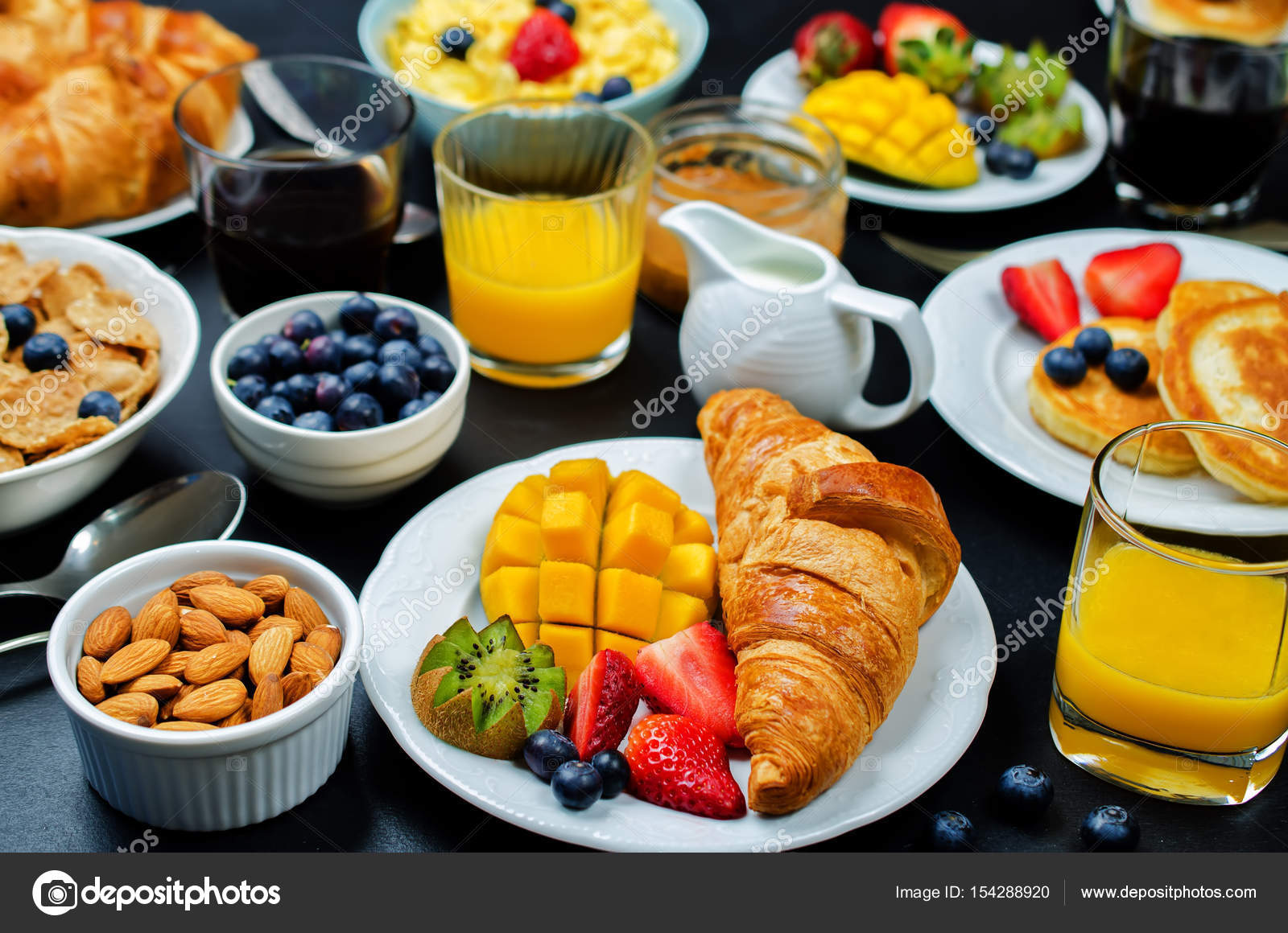 Breakfast table setting with flakes, juice, croissants, pancakes ...