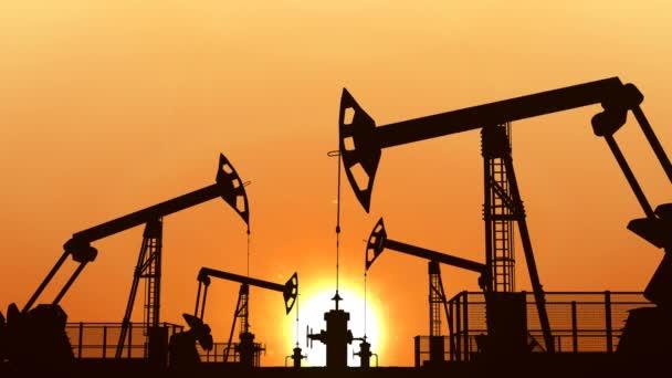 Looped oil pumpjacks against orange sunset sky