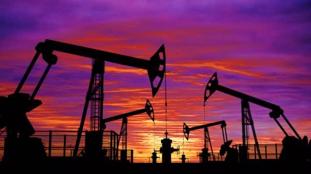 Cyklických ropy pumpjacks proti růžové západu slunce na obloze