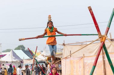 PUSHKAR, RAJASTHAN / INDIA - NOVEMBER 2019 : Young girl performing acrobatics in tight rope and balancing with bamboo at Pushkar Fair
