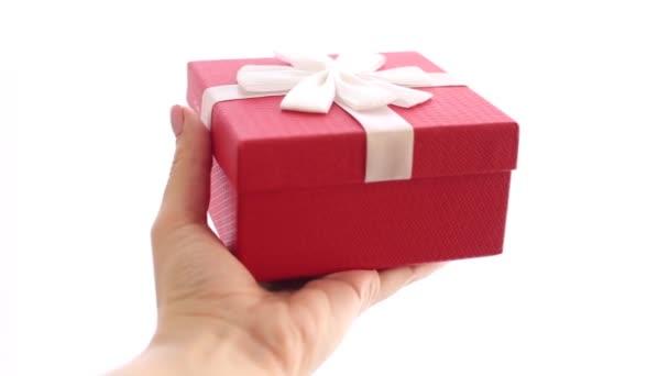 Dámská ruka drží červenou dárkovou krabičku s bílou mašlí nahoře.