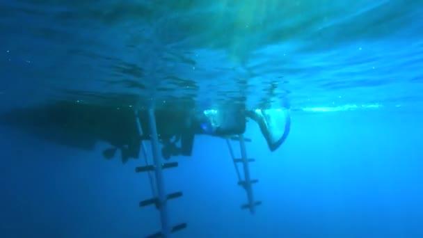 zpomalený záběr potápěčů skákajících z člunu