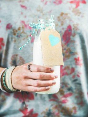 woman holding bottle of milk
