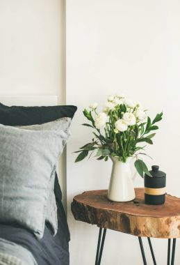 Trendy Scandinavian style interior shot. Bedroom with washed linen grey pillows and wooden nightstand with bucket of flowers and candle stock vector
