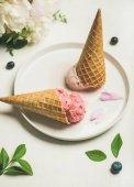 Fotografie Růžová jahody a kokosové kopečky zmrzliny, sladké šišky a Pivoňka kytice na štítku nad bílým pozadím