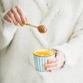 Zdravá Veganská kurkuma latte nebo zlaté mléko s medem v ženských rukou