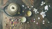 Fotografie Tradiční Asijská čajový obřad uspořádání. Železo konvice, šálky, sušené růže poupata a květy kvetoucí mandloň dřevěný stůl pozadí