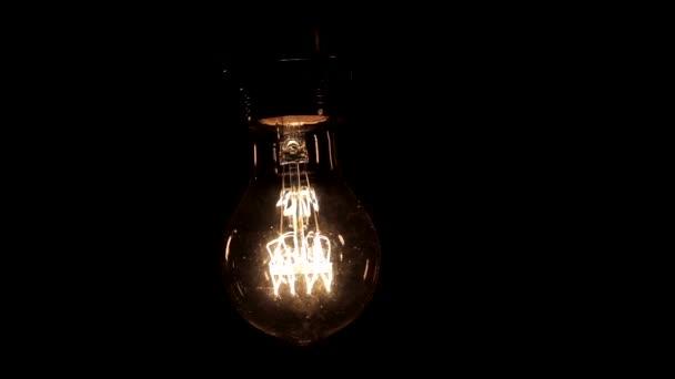 Detailní záběr lampy Edison s teplým světlem lehce houpe na černém pozadí