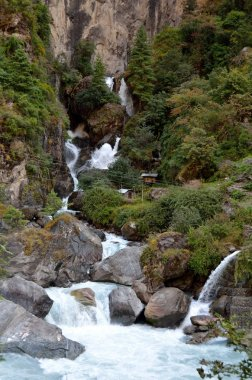 Cascading waterfall in the mountains among large stones, Himalayas