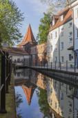 Fotografie Memminger Park, wo sich ein Fluss spiegelt, in dem sich die typisch deutschen Gebäude widerspiegeln