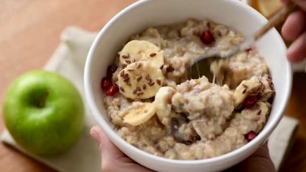 Haferbrei Schüssel für ein gesundes vegetarisches Frühstück. Unerkennbare Person, die Hafer isst. Nahaufnahme