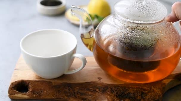 Nalít čaj do šálku. Uvařený černý čaj ve skleněné čajové konvice. Horký nápoj čínský čaj
