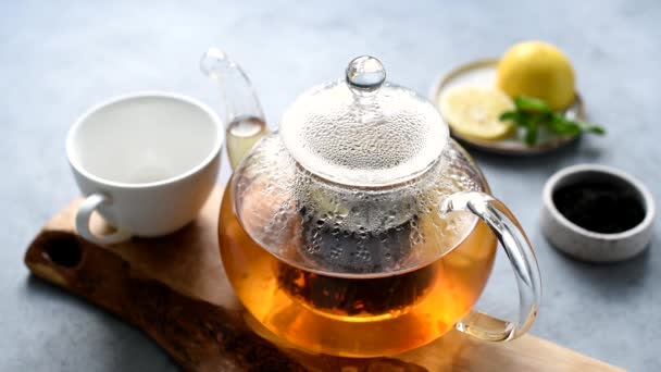 Person pouring black tea in a cup. Glass tea pot with freshly brewed black tea with lemon and mint leaf
