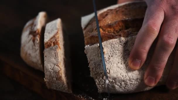 Slicing sourdough white bread on a dark wooden background. Slow motion of cutting bread with a knife
