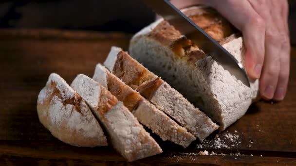 Osoba krájení kysaného chleba detailní pohled. Záběry muže krájejícího bílý kysaný chléb na dřevěné řezací desce