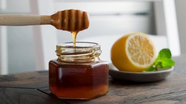 Tekutý med ve sklenici. Namáčení dřevěné medové lžičky ve sklenici zlatého květinového medu. Zdravé jídlo