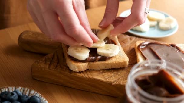 Žena připravuje čokoládový toast s banánem. Zdravá veganská vegetariánská snídaně nebo oběd nebo sladká svačinka