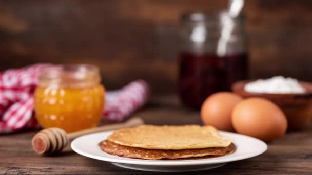 Blini nebo palačinky s medem a džemem na rustikálním dřevěném stole. Zastavte animaci pohybu stohu ruských blinisů, tenkých palačinek nebo krepu. Rozlišení 4k
