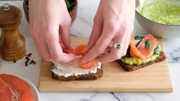 Making a sandwich with cream cheese, smoked salmon and spinach. Healthy rye bread sandwich or toast with fish. Rich in omega 3 snack, appetizer or breakfast