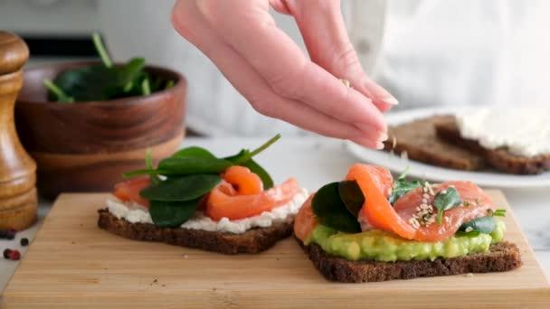 Zdravé žitné chlebíčky s avokádem Losos a semínka. Pomalý pohyb kuchaře zdobení potravin se semeny konopí. Bohaté na Omega 3 mastné kyseliny potravin