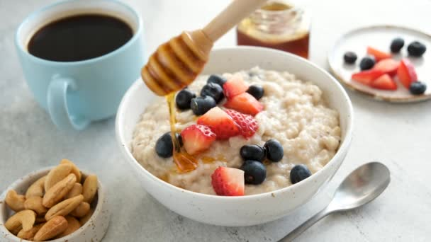 Oatmeal porridge with honey and berries. Person adding natural honey to oatmeal porridge with fresh berries. Concept of healthy eating, healthy lifestyle, dieting and weight loss