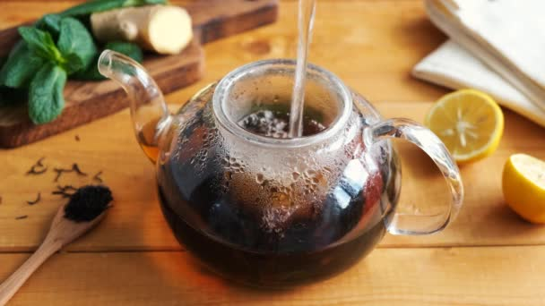 Brewing black tea with ginger lemon and mint in glass tea pot, wooden table background. Healthy herbal tea anti flu and immune boost