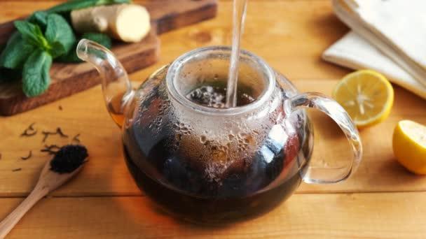 Pivovarský černý čaj se zázvorovým citrónem a mátou ve skleněném čajovém hrnci, dřevěné zázemí stolu. Zdravý bylinný čaj proti chřipce a posílení imunity