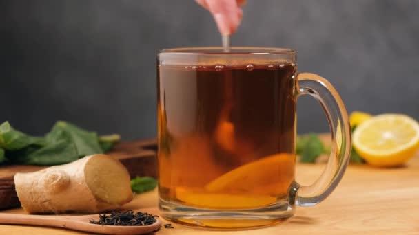 Cup of ginger lemon tea. Stirring tea with spoon