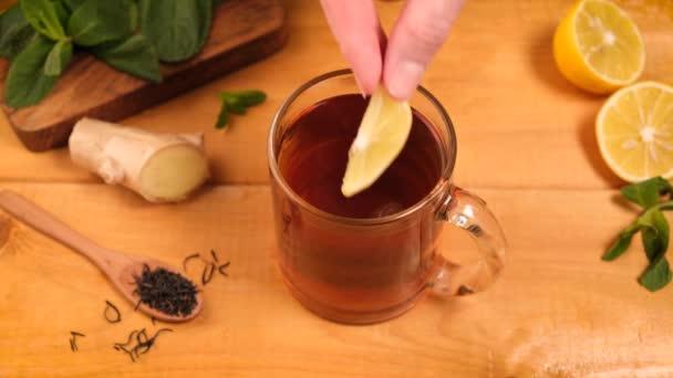 Přidávám citron do šálku zázvorového čaje. Zdravý nápoj proti chřipce na dřevěném stole. Alternativní medicína bylinný čaj