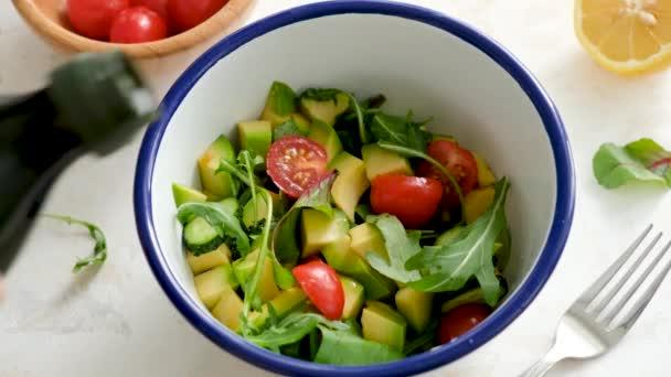 Oblečovací salát s olivovým olejem. Zdravý zelený zeleninový salát s avokádem, rajčaty a okurkou se obléká olivovým olejem