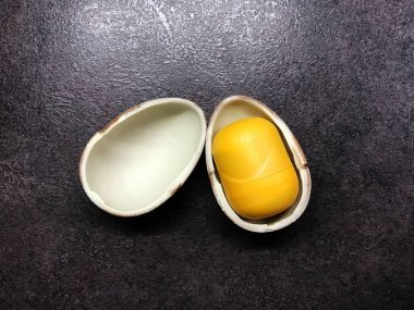 Easter open chocolate kinder egg with a yellow core on a black table
