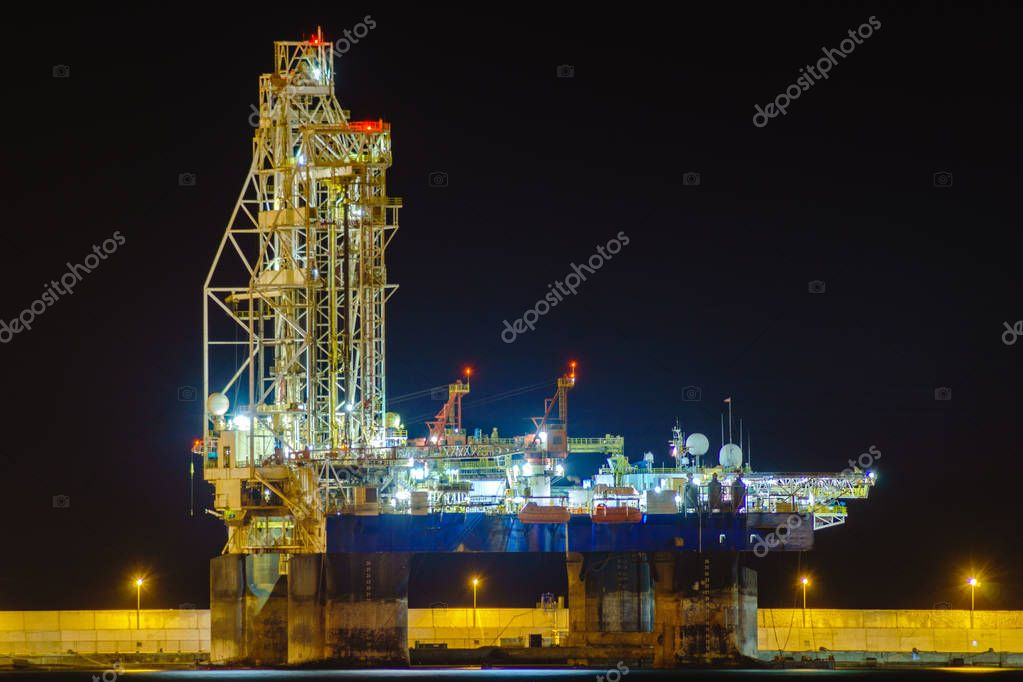 Drilling platform at night in the port stock vector