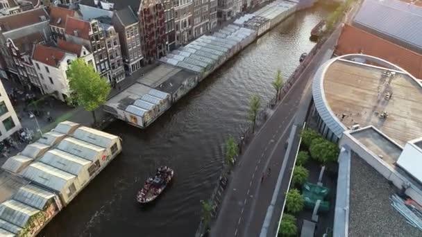 Amsterdam, Nizozemsko, 4K. Letecký výhled nad kanálem a starým centrem okresu. Slavné Amsterdam kanály, party lodě a typické holandské domy. Panorama města a ulic v krásných teplých barvách.