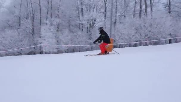 Profesionální lyžař sjíždí ze svahu. Krásná zimní bílá scenérie, stromy pokryté sněhem. Lyžař jezdí rychle v klasickém lyžařském stylu.