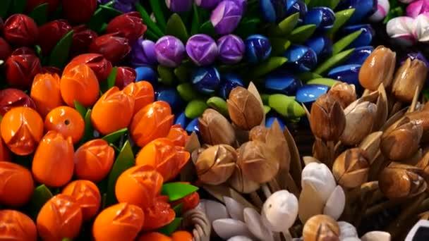 Detailní záběry barevných tulipánů v turistickém obchodě v centru Amsterdamu v Nizozemsku. Typický holandský obchod, malý obchoďák v centru města, s pěknými dřevěnými suvenýry, pohlednicemi a magnetickými kartami.