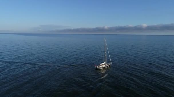 Luftaufnahme eines schönen Segelbootes oder einer Jacht, die nach Sonnenaufgang in die ruhige See hinaussegelt. Ostsee in Polen, Sommersaison. Einsamer Matrose mitten auf dem Meer