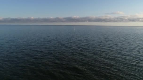 Aerial view of wide sea and beautiful sailboat or a yacht sailing out into the calm sea after sunrise. Baltic sea in Poland, summer season. Lonely sailor in the middle of the sea