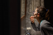 Young and beautiful woman looking at her gums in a bathroom mirror. she is in profile and has glasses