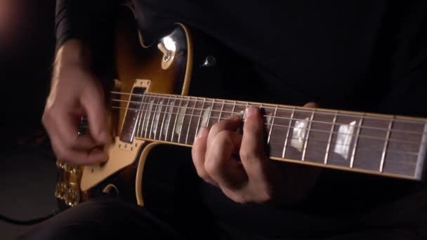 kytarista hraje na kytaru ve studiu. Zpomalit o 100 pencí. tmavé pozadí