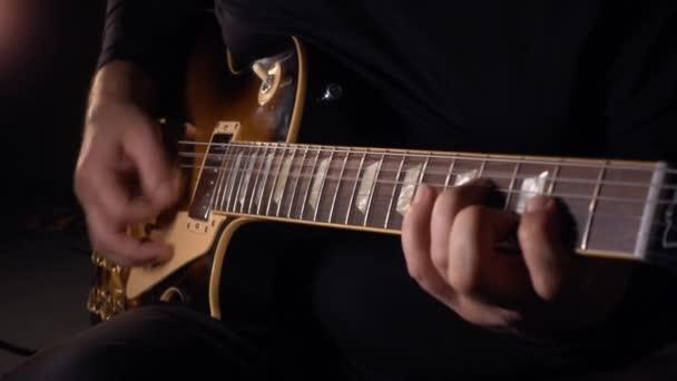 Kytarista hraje na kytaru ve studiu na desce. Zpomalený pohyb 50p
