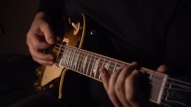 Kytarista hraje na kytaru ve studiu na desce. Zpomalený pohyb 100p