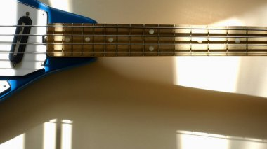 Old vintage bass guitar in the sun light . Color background . Copy space