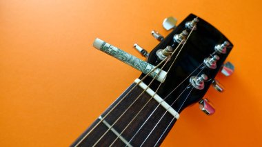 guitar headstock and dollar bill twisted into a straw . color background with copy space