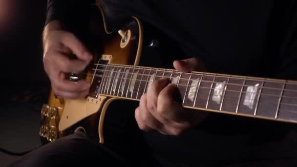 Kytarista hraje na kytaru ve studiu na desce .