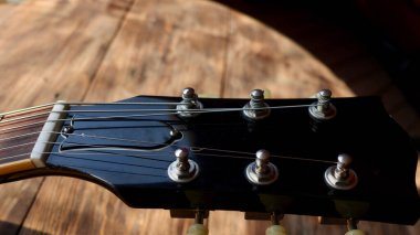 Vintage electric guitar headstock on the wooden boards