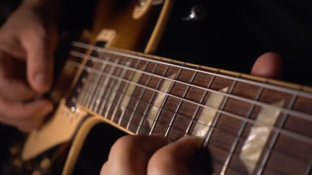 Kytarista hraje na elektrickou kytaru. Zpomalený pohyb 50p