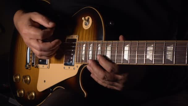 Kytarista hraje na elektrickou kytaru. Zpomalený pohyb 100p